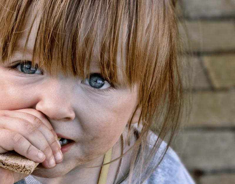 povertà in italia. bambina piccola mangia un pezzo di pane