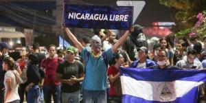 crisi umanitaria nicaragua - giovane a volto coperto con in mano un cartello con su scritto Nicaragua libre